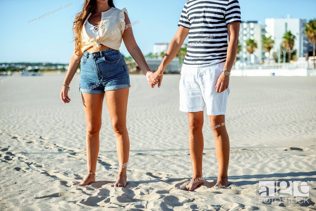 Stock Photo: Close-up of couple holding hands on the beach.
