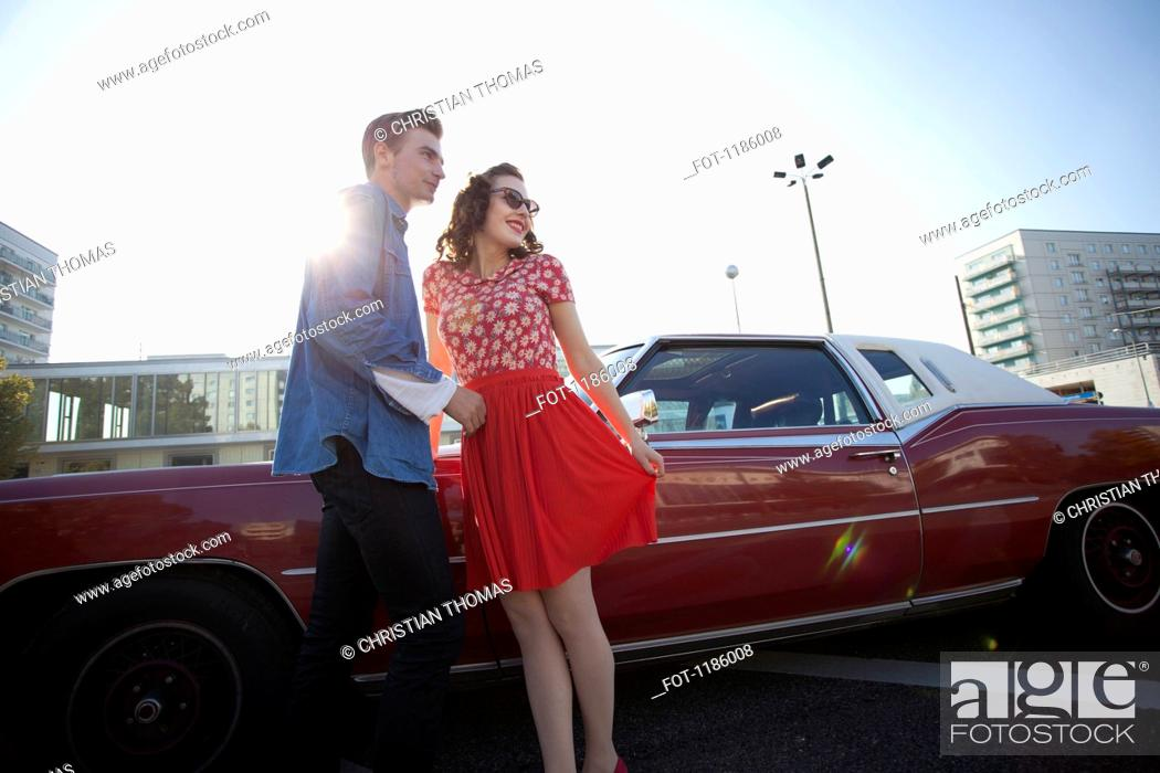 Stock Photo: A cheerful rockabilly couple standing next to a vintage car.