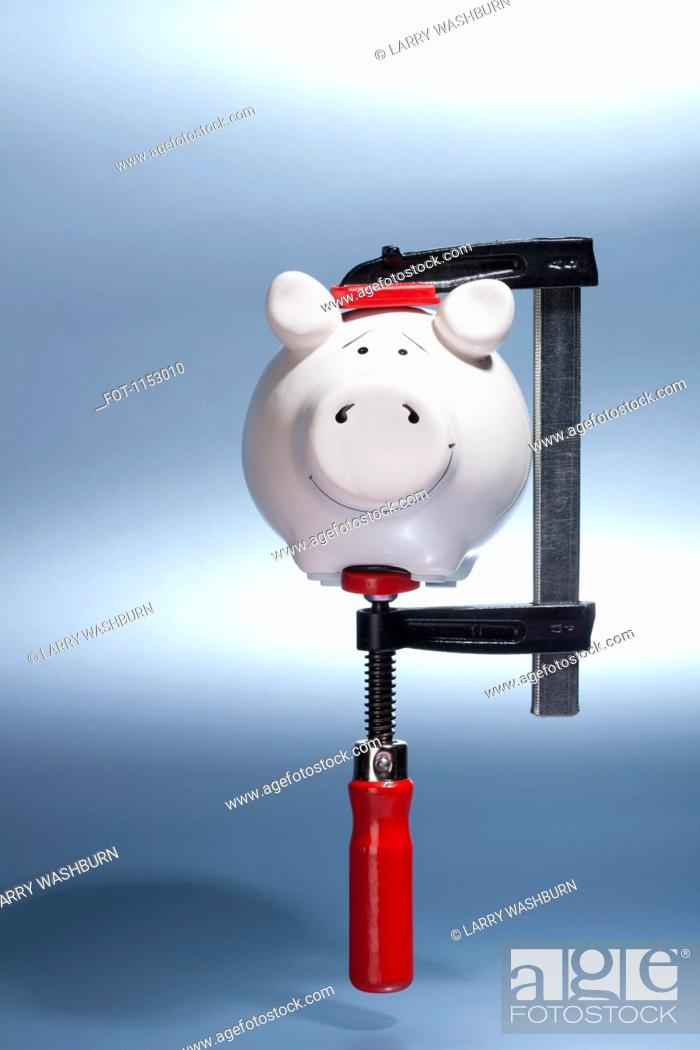 Stock Photo: A piggy bank being held in a vise grip suspended in mid-air.