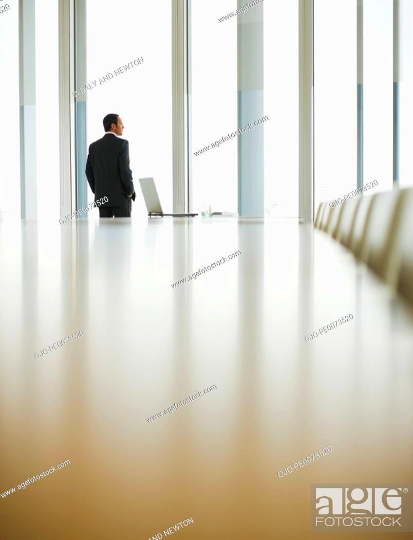Stock Photo: Businessman standing at window of empty conference room.