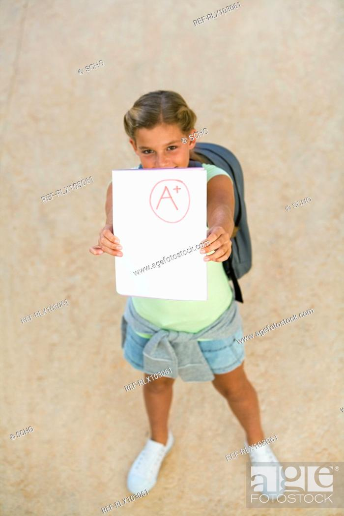 Stock Photo: Girl 10-13 holding up test paper with A+ mark on it, from above.