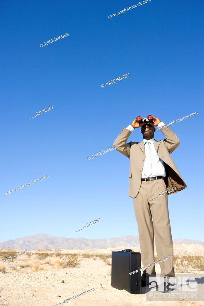 Stock Photo: Businessman by briefcase using binoculars in desert, low angle view.
