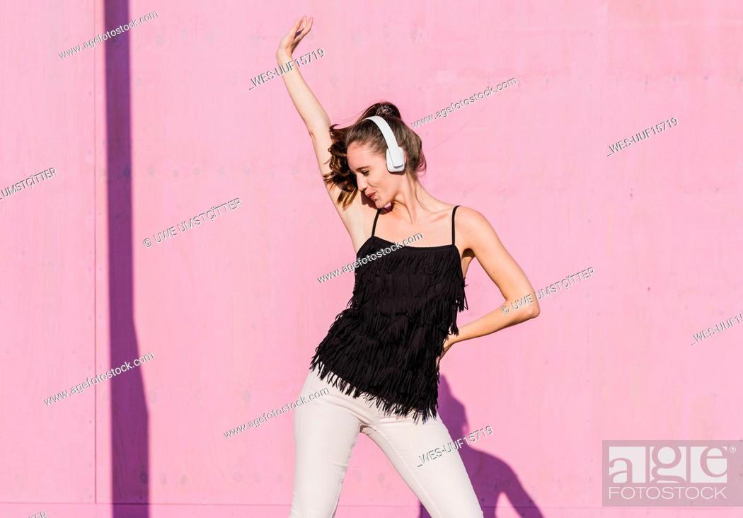 Imagen: Happy young woman wearing headphones dancing in front of pink wall.