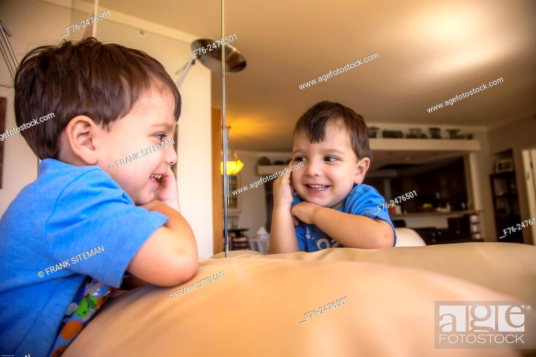 Stock Photo: portrait of 3 year old boy, amusing himself by playing with his image in a mirror.