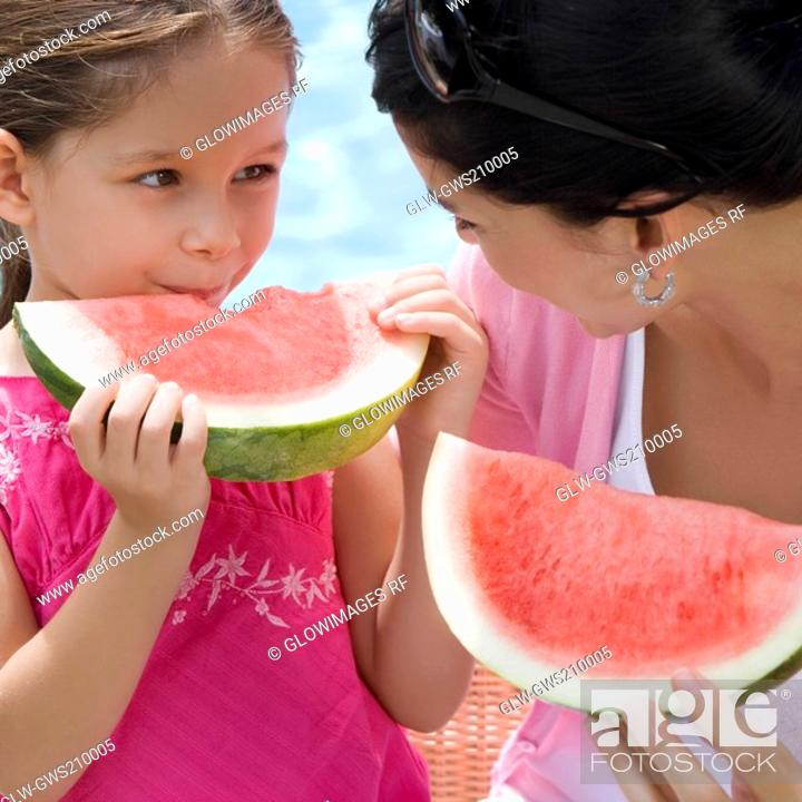 Stock Photo: Close-up of a young woman with her daughter eating watermelon slices.