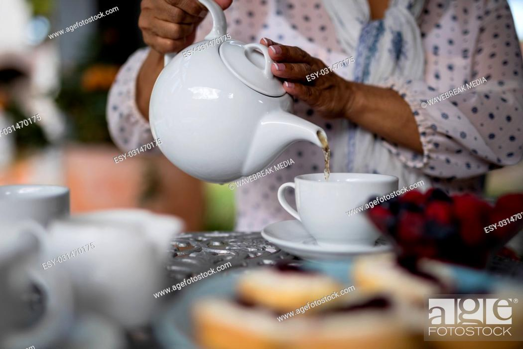 Stock Photo: Mid section of woman pouring tea in cup.