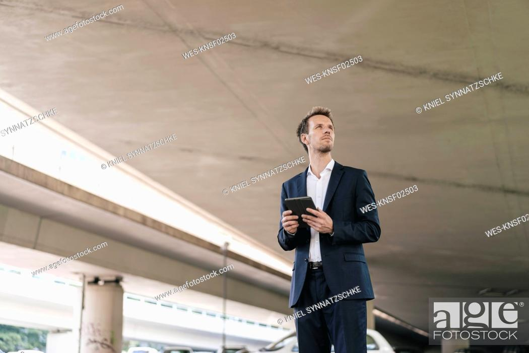 Stock Photo: Businessman standing at underpass holding tablet.