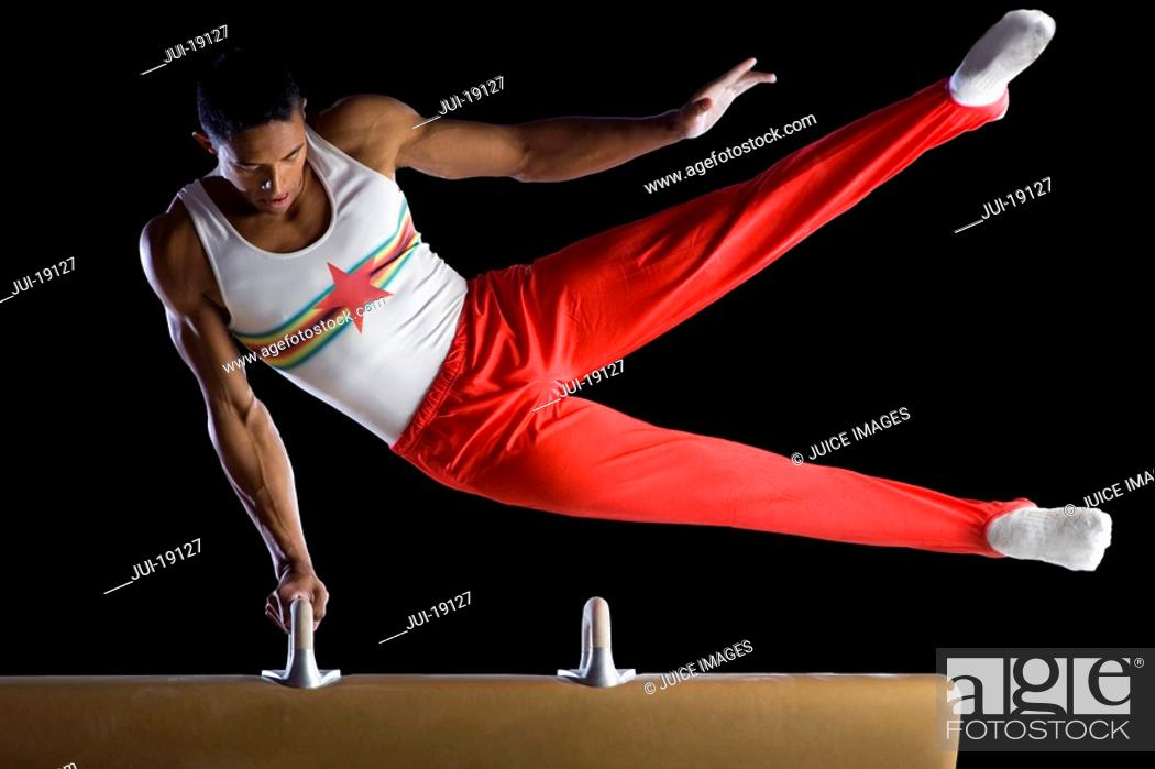 Stock Photo: Male gymnast performing on pommel horse, low angle view.