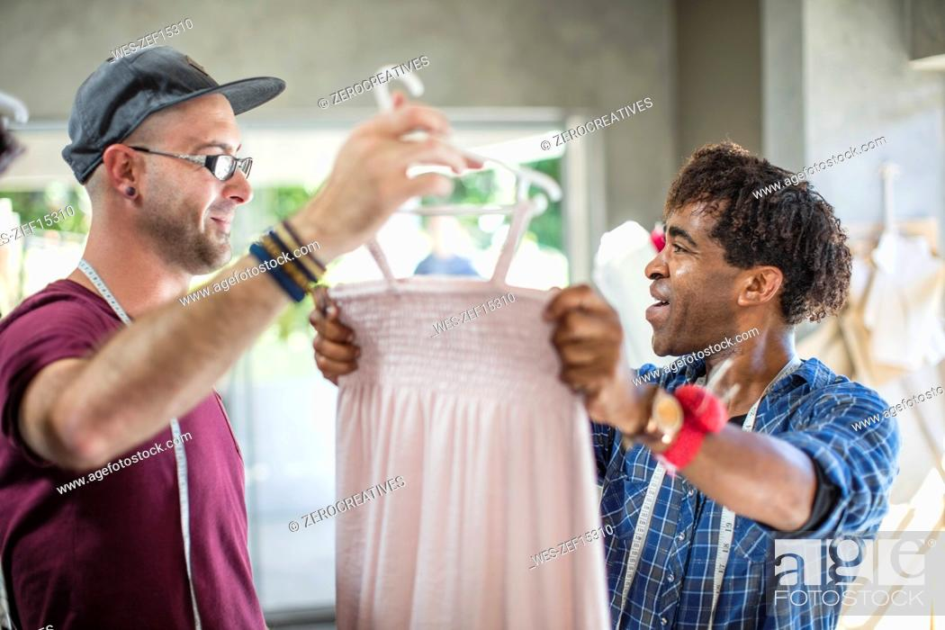 Stock Photo: Smiling fashion designer showing dress to colleague.