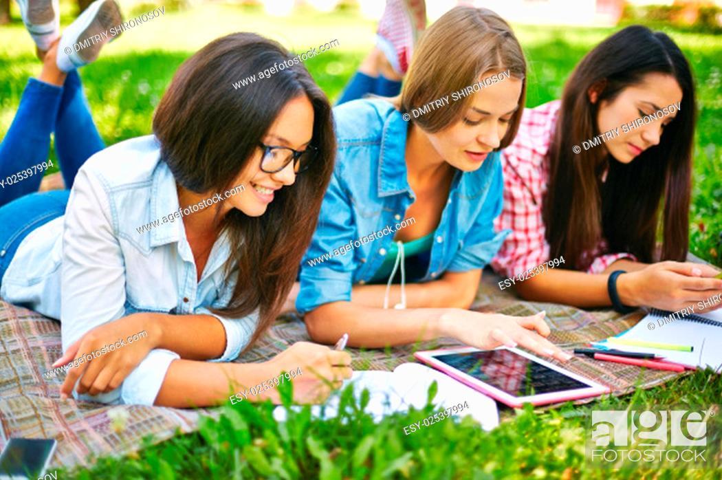 Stock Photo: Modern teen girls doing schoolwork outside.
