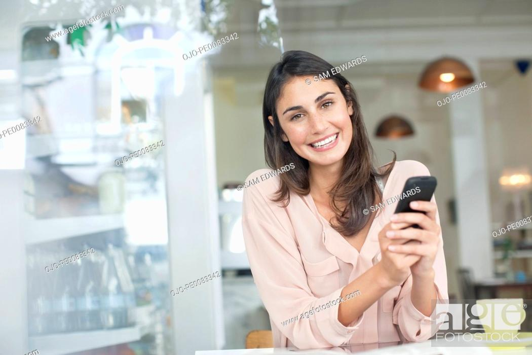 Stock Photo: Portrait of smiling woman holding cell phone in café window.