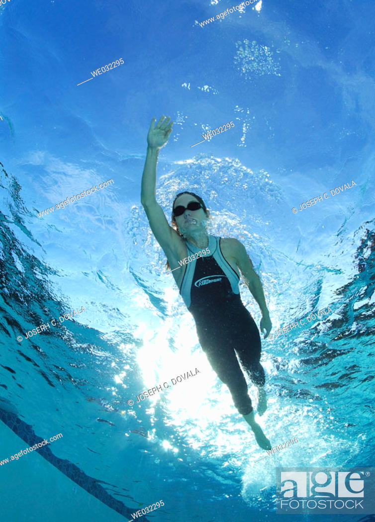 Stock Photo: Swimmer from underneath in pool.