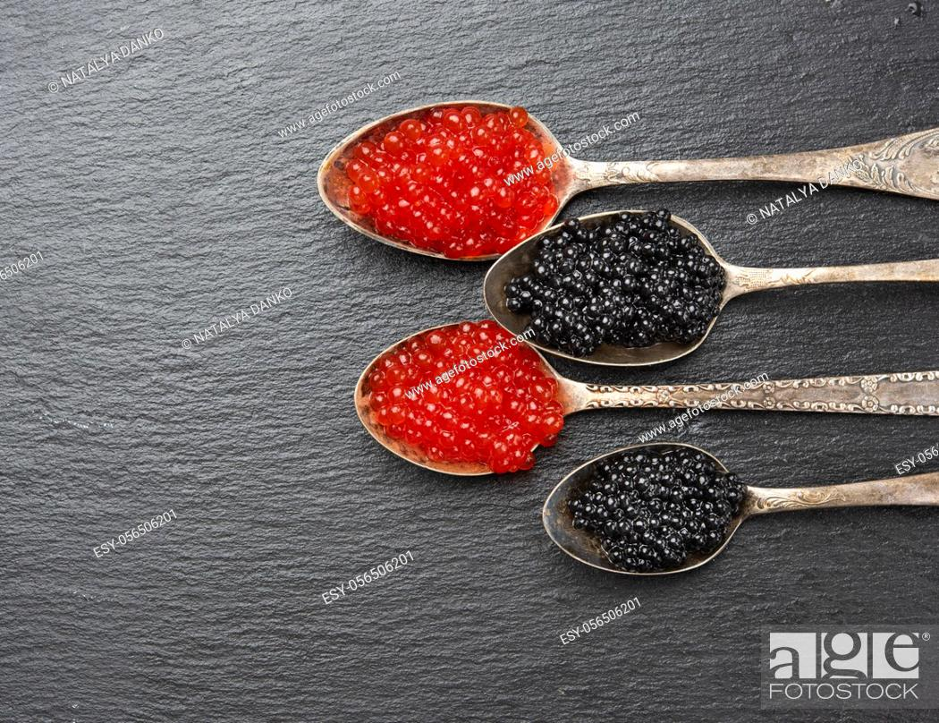 Stock Photo: caviar of paddlefish fish and red chum salmon caviar in a spoon, black background, top view.