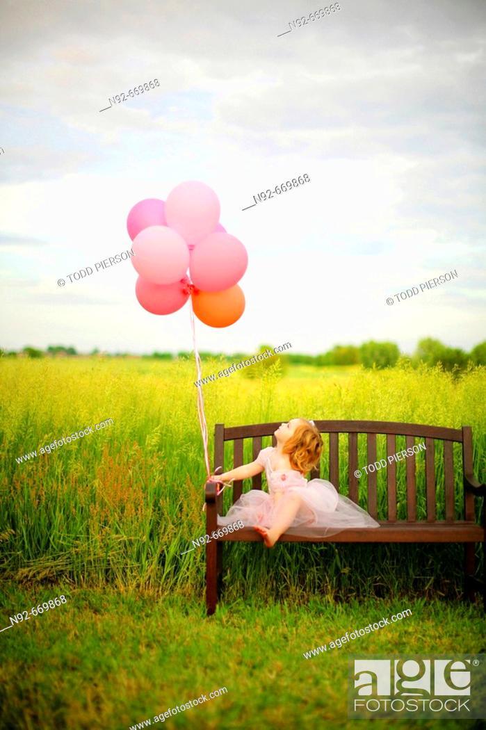 Stock Photo: Girl, age 3 looking at balloons.