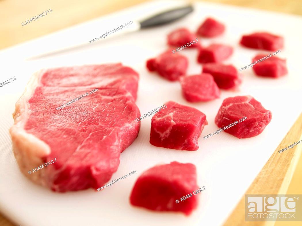 Stock Photo: Cubed raw steak on cutting board.
