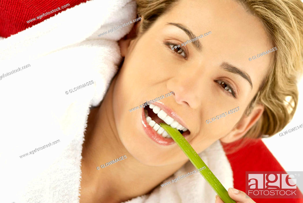 Stock Photo: Portrait of a young woman eating an asparagus.