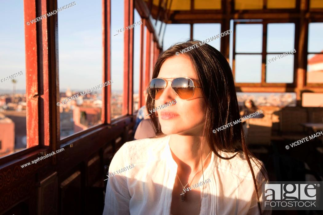 Stock Photo: Nice woman in a Marrakech's restaurant looking through the window.