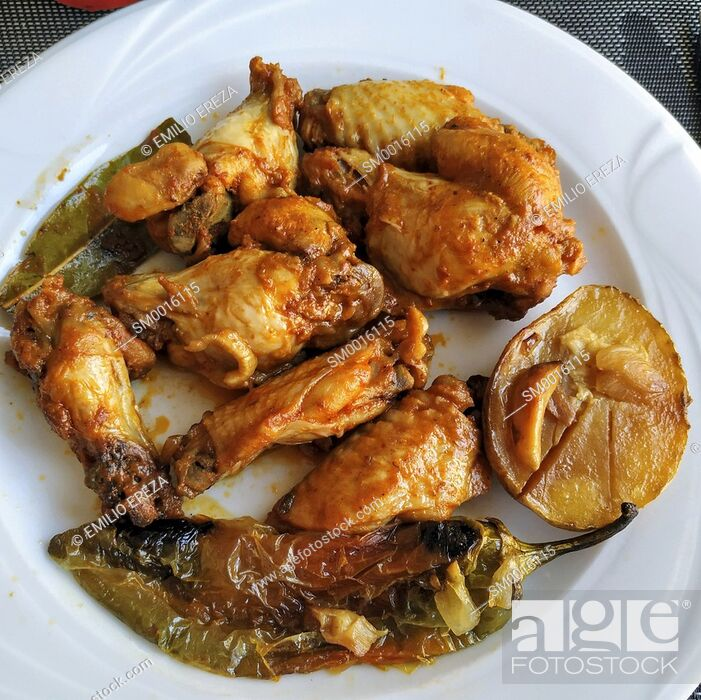 Stock Photo: Chicken wings with potatoes and peppers.