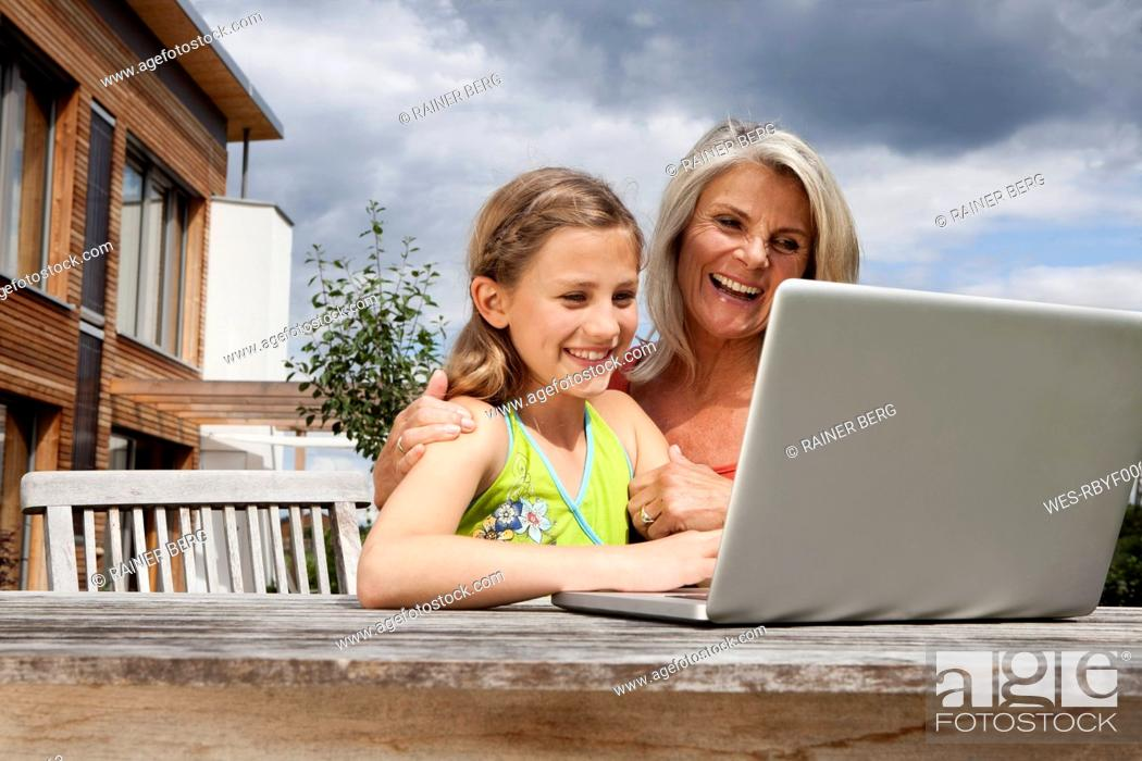 Stock Photo: Germany, Bavaria, Nuremberg, Grandmother and granddaughter using laptop.