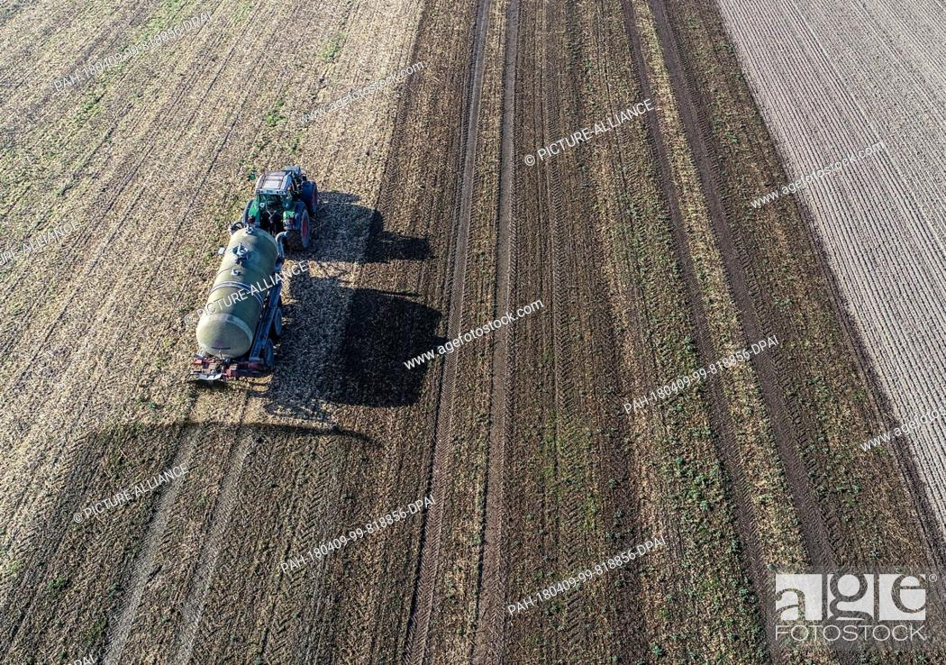 Stock Photo: 09 April 2018, Germany, Sieversdorf: Fermentation residues from a biogas plant are spread on a field (taken with drone). The residues which remain after the.