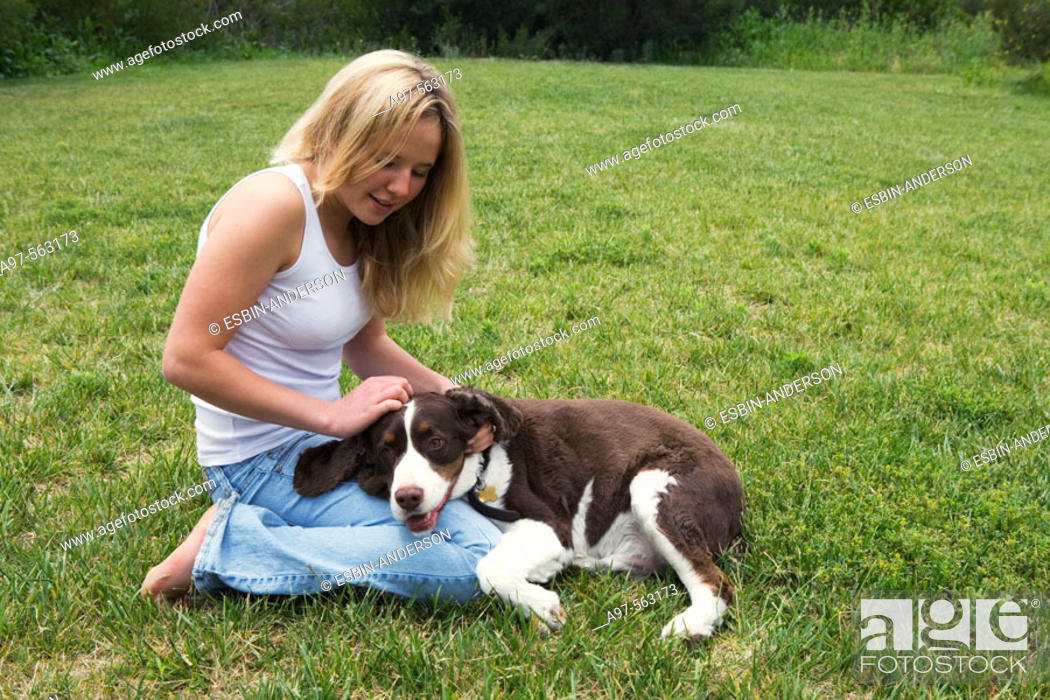 Stock Photo: Smiling blonde teen girl in blue jeans and white tank top kneeling on grass lawn, pets her dog's head resting on her leg.
