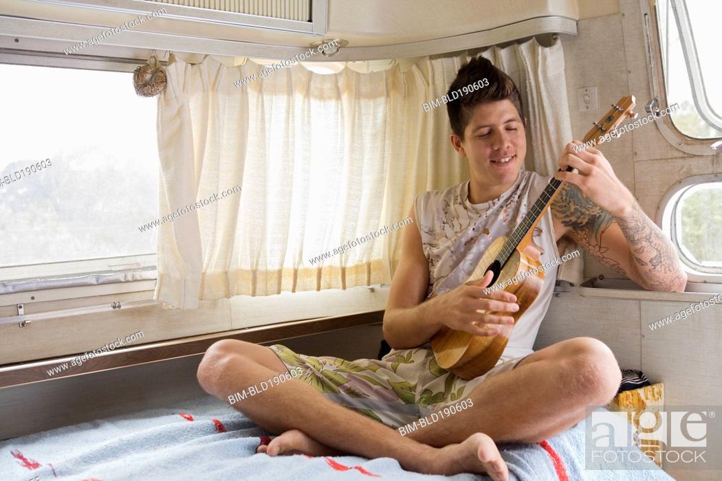 Imagen: Mixed race man playing ukulele.