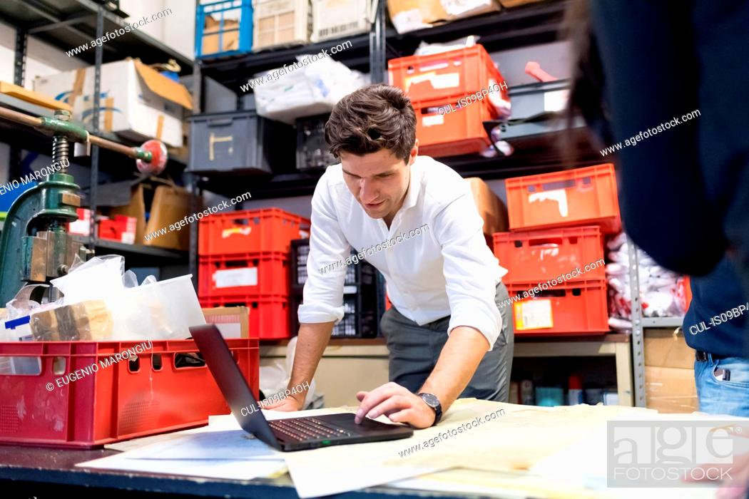 Stock Photo: Man using laptop in demonstration in warehouse.