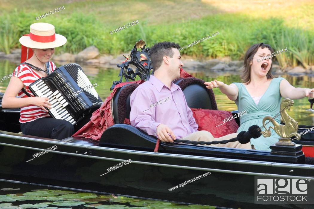 Imagen: Mid adult man looking at a mid adult woman singing in a gondola.