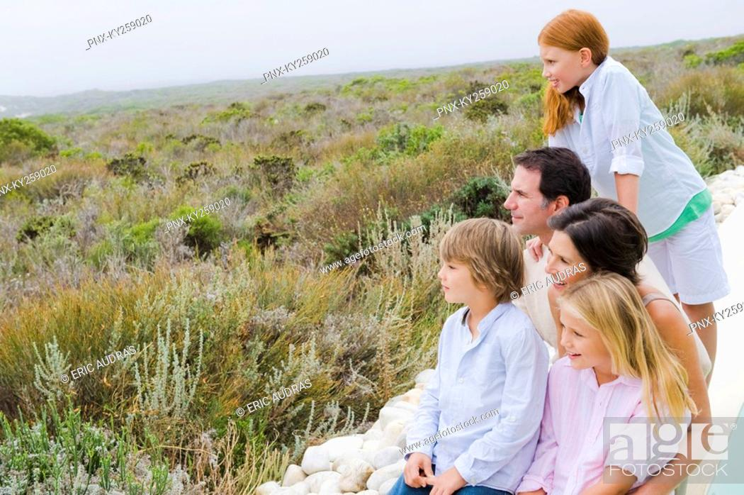 Stock Photo: Family sitting at the poolside and admiring the view.