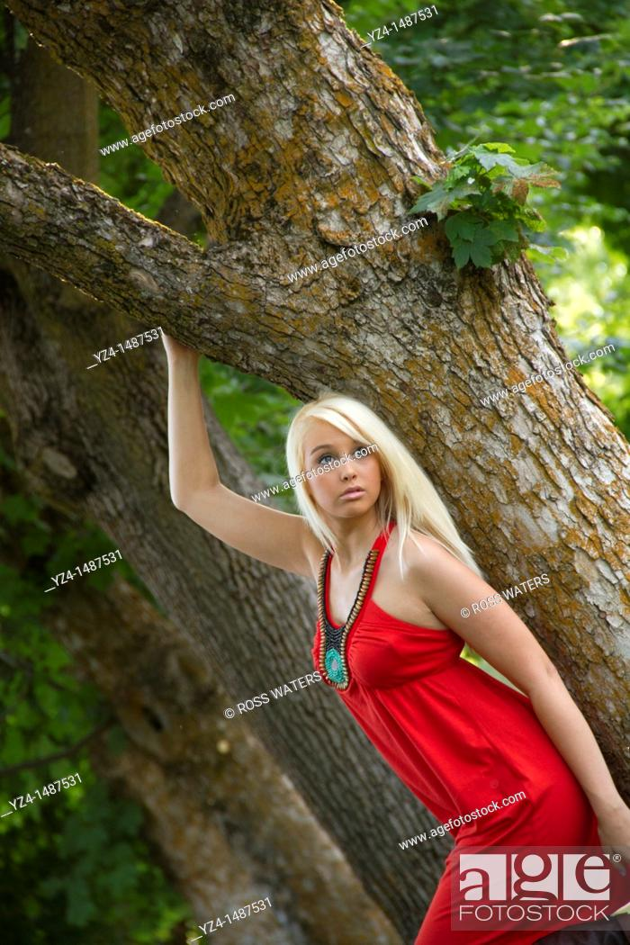 Stock Photo: A young woman in a red dress outdoors.