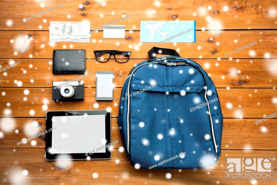 Stock Photo: travel, tourism, winter holidays and objects concept - close up of smartphone with tablet pc computer, airplane ticket and personal stuff.