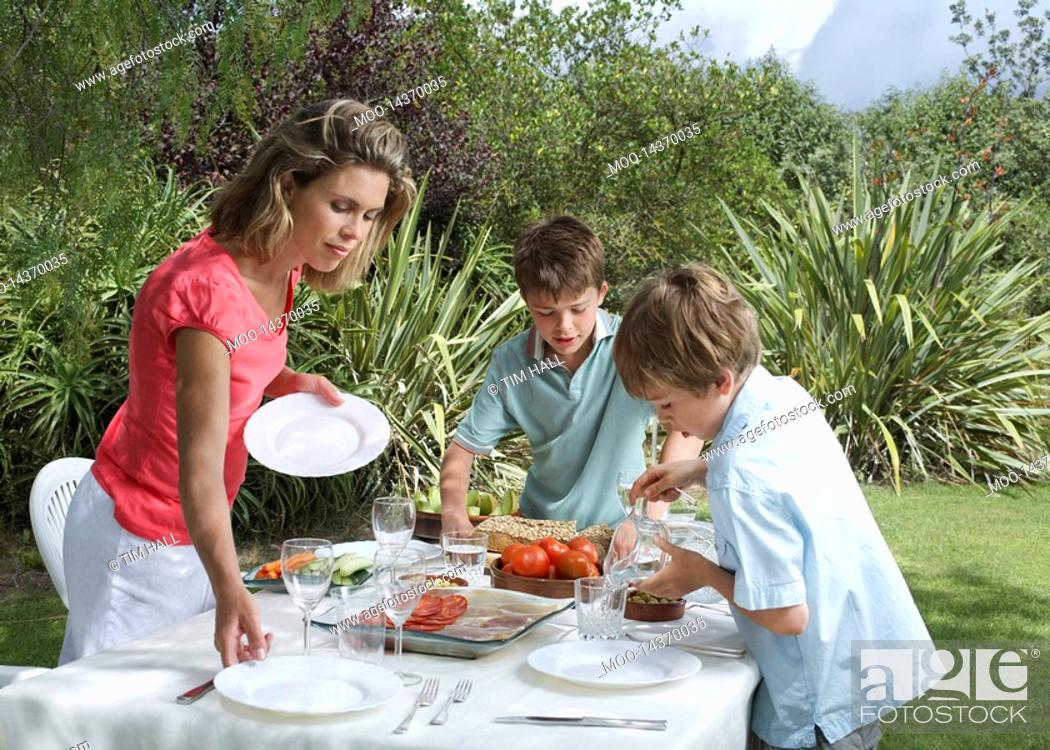 Stock Photo: Mother and two sons 6-11 laying dinner table in garden.