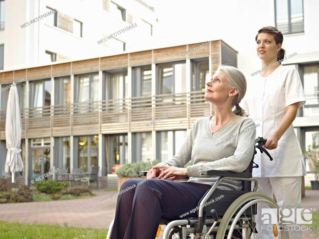 Stock Photo: Germany, Cologne, Caretaker pushing senior women in wheelchair.