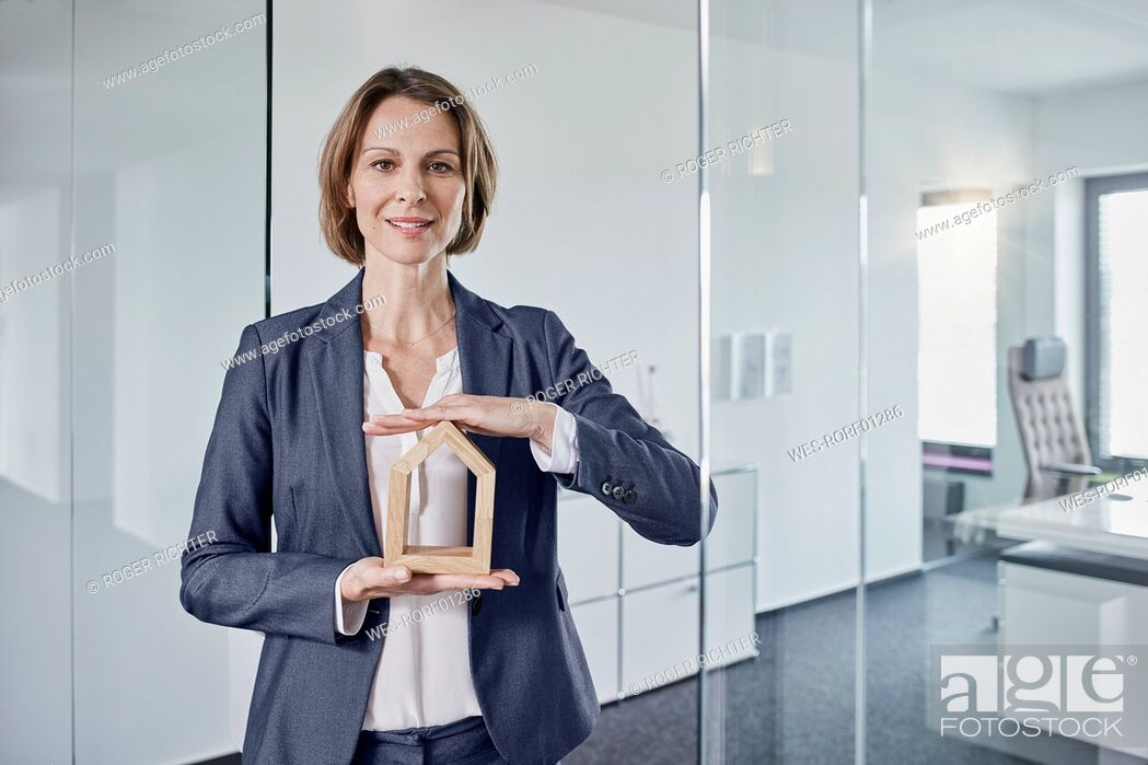 Imagen: Portrait of businesswoman holding architectural model in office.