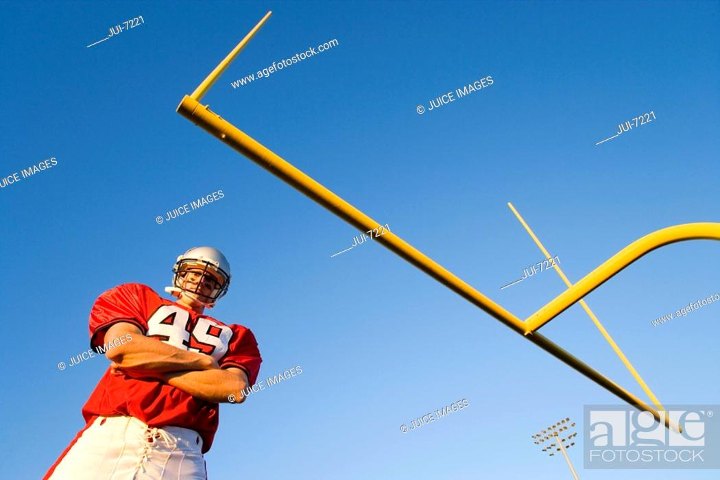 Stock Photo: American football player, in red football strip and protective helmet, standing below goal post, arms folded, portrait, low angle view.