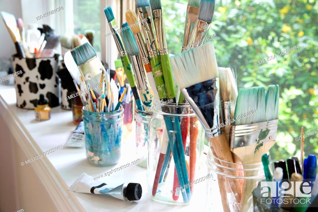 Stock Photo: Row of jars with variety of artist paintbrushes on window sill of artists studio.