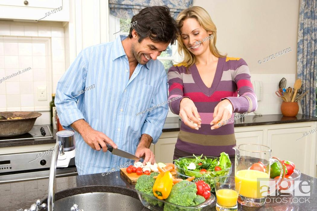 Stock Photo: Man and woman making salad, smiling.