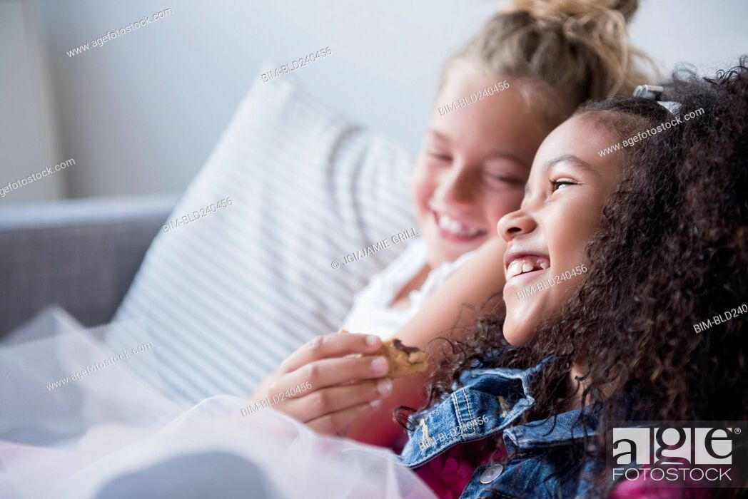 Stock Photo: Smiling girls eating cookie on sofa.
