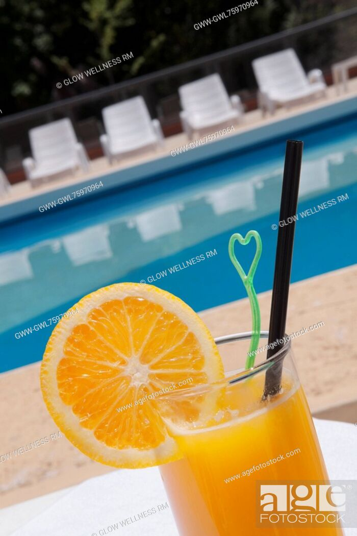 Imagen: Glass of orange juice at the poolside.