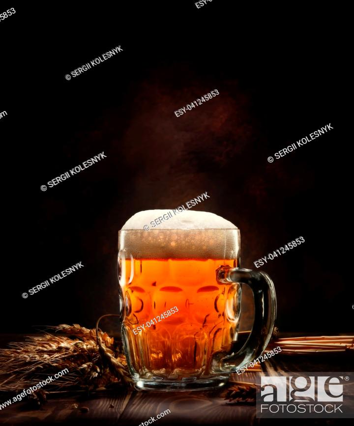 Stock Photo: Beer in mug and wheet on wooden table and black background.