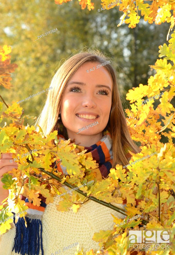 Stock Photo: Portrait on a young smiling woman in a autumn colored forest in Ystad, Scania, Sweden.