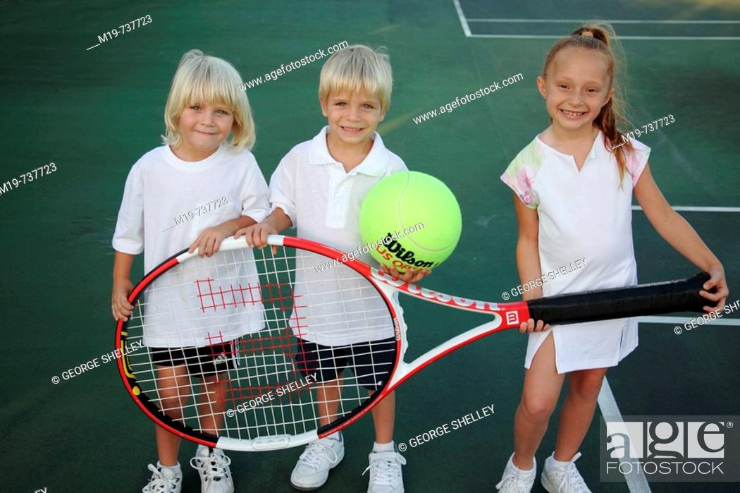 Stock Photo: Kids posing with an oversized tennis racket and ball.