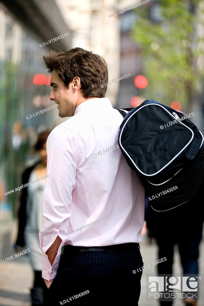 Stock Photo: A businessman walking, carrying a gym bag.