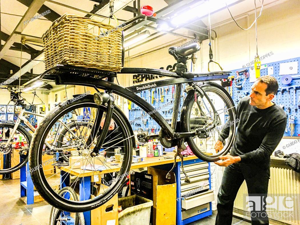 Stock Photo: Tilburg, Netherlands. Huge, Double Dutch Transport Bike Undergoing Tubular Maintenance.