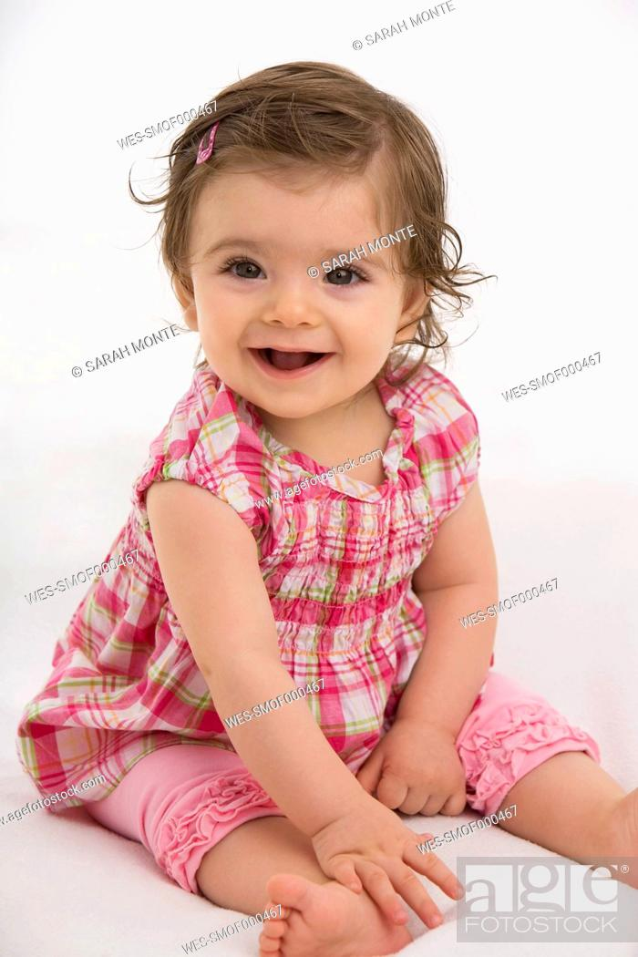 Stock Photo: Baby girl sitting, smiling, portrait.