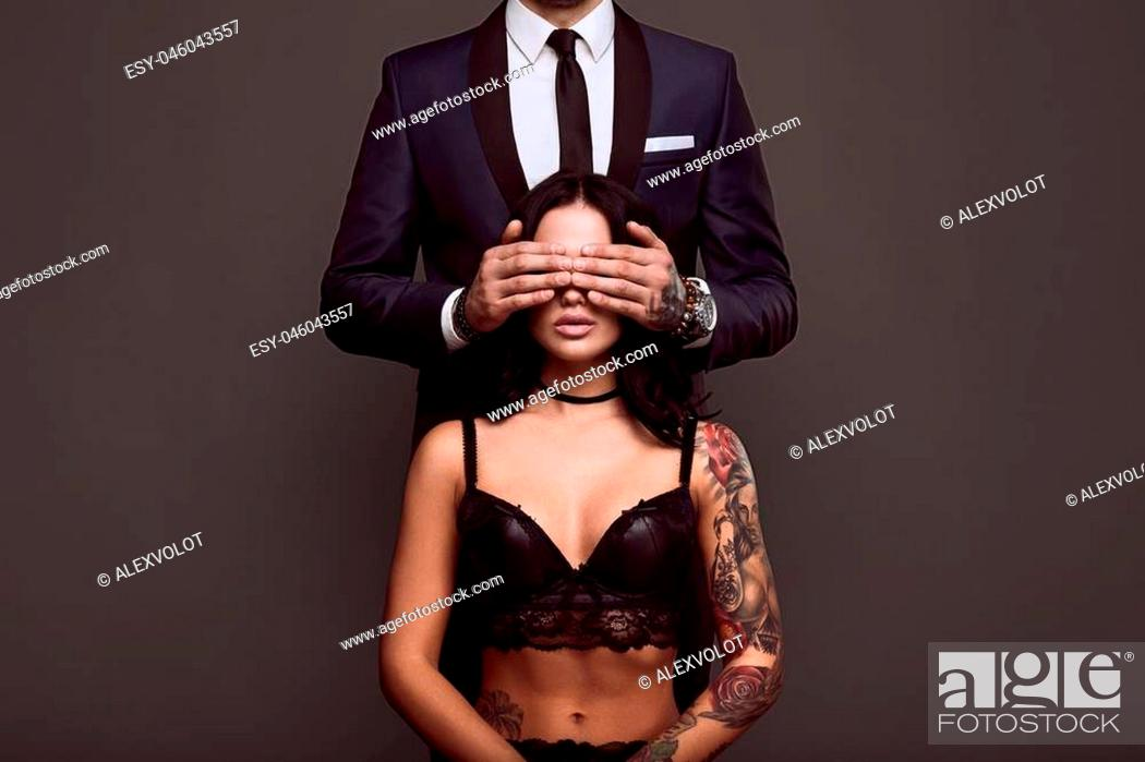 Stock Photo: Portrait of a brutal man in elegant suit touches sexy girl with a tattoo in lingerie on gray background.