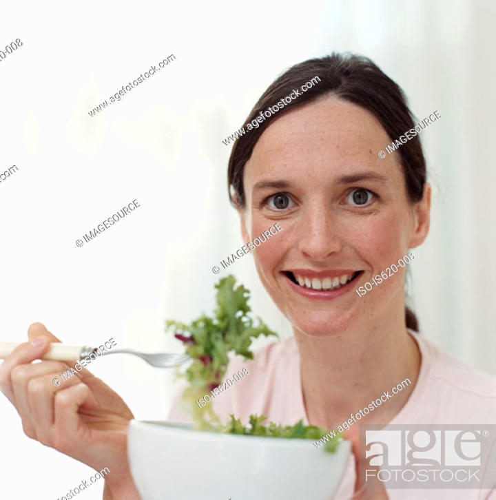 Stock Photo: Smiling woman eating salad.