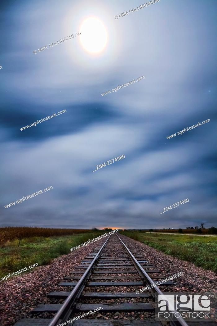 Stock Photo: Fog blows west off the hills in western Iowa above train tracks lit by the moon which also had a vivid corona.