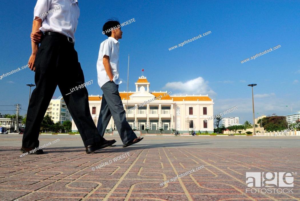 Stock Photo: Walking past 'Nha Van Hoa', Nha Trang's Vietnamese Cultural House located at the beach promenade Tran Phu,  Nha Trang, Vietnam.