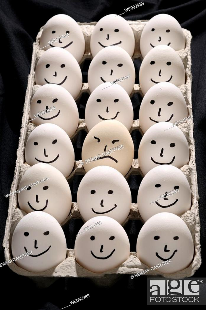 Stock Photo: Package of backlit eggs on black cloth with smiling faces except for one grumpy sad face.
